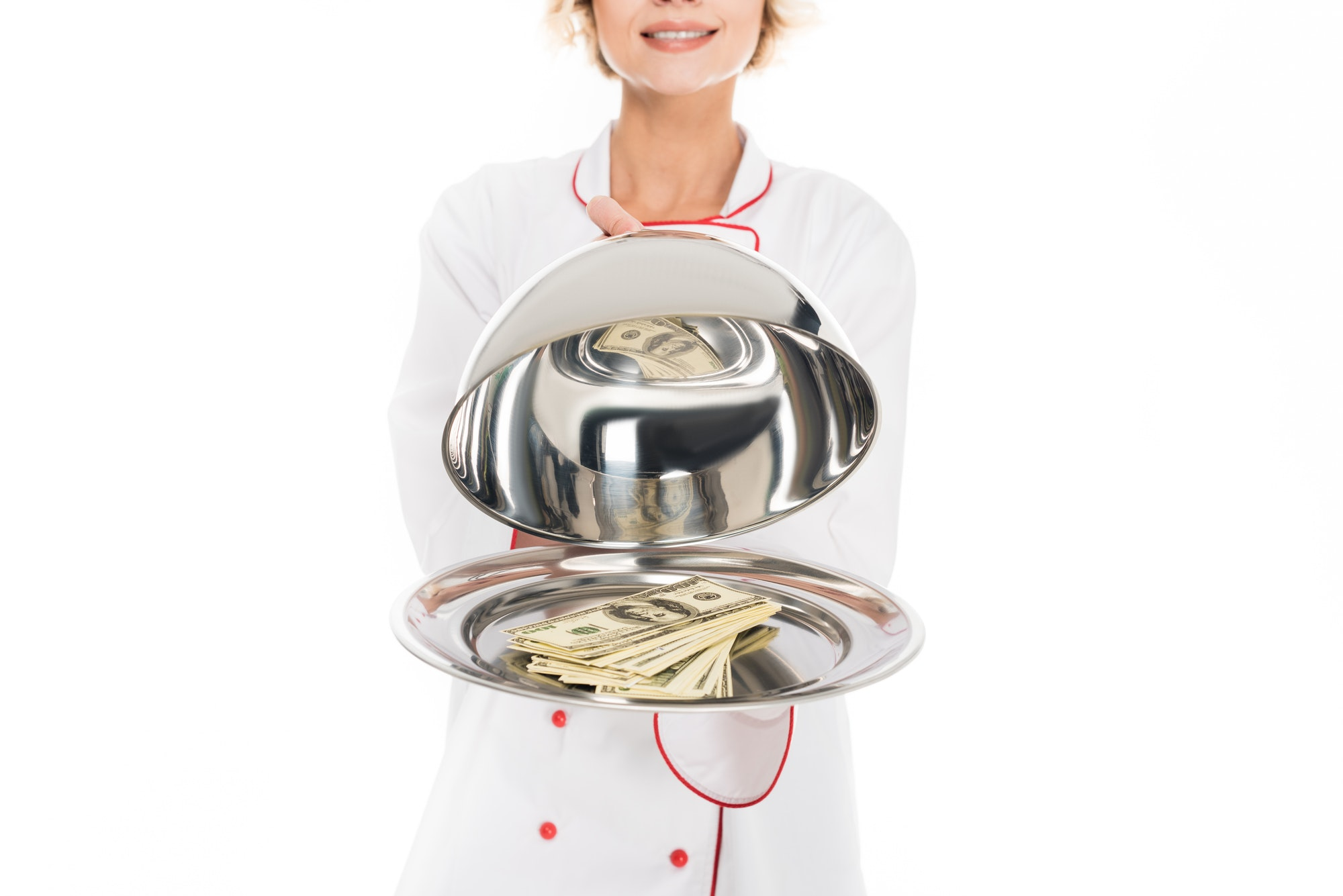 cropped shot of chef holding serving tray with money in hands isolated on white